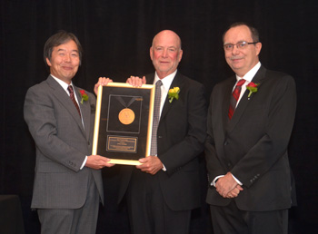Hironori Kasahari (left) and Paolo Montuschi (right) present Sorel Reisman with the Richard E. Merwin Award for Distinguished Service.