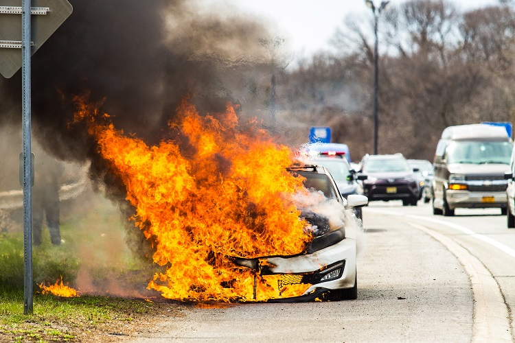 Burning car on fire on a highway road accident at day