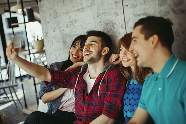 guy taking selfie with friends