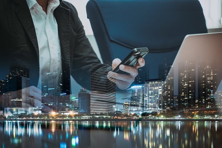 Double exposure of businessman holding smartphone and touching it and city in business,communication and technology concept