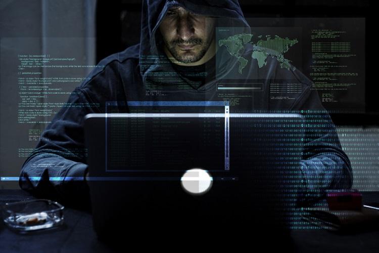 man wearing hoodie in dark room on laptop