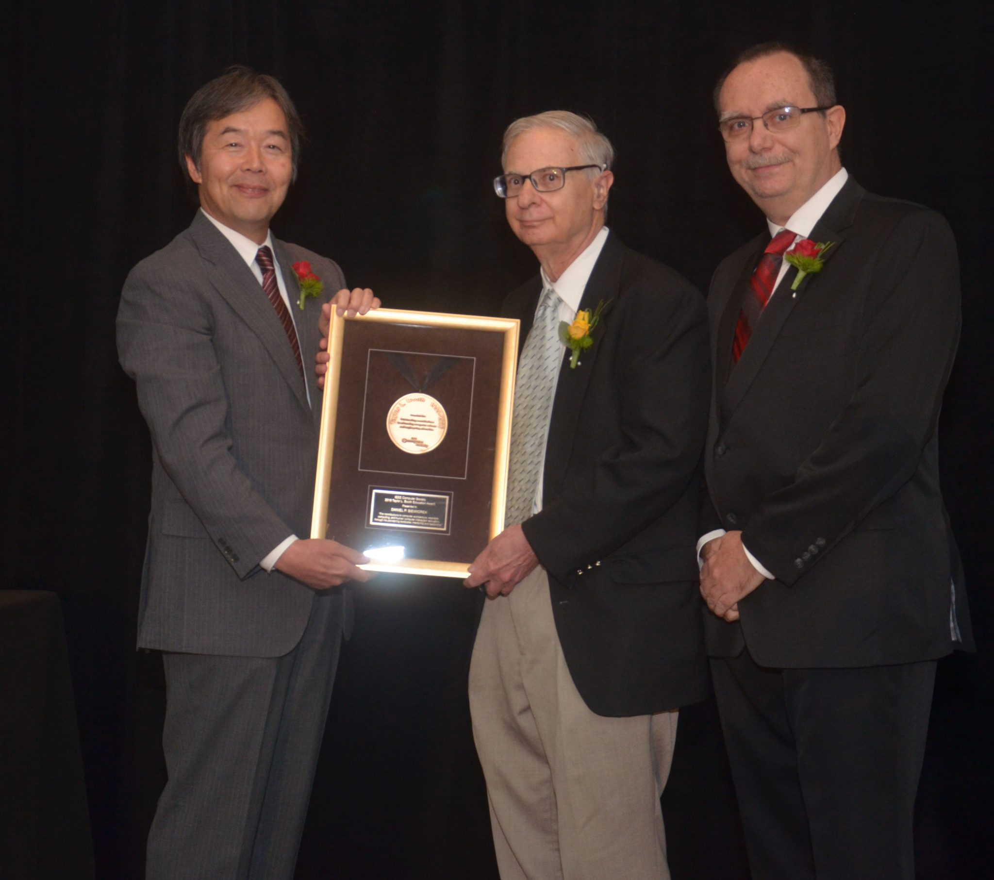 Daniel P. Siewiorek (center), Buhl University Professor of Electrical and Computer Engineering and Computer Science at Carnegie Mellon University, accepts the 2018 recipient of the IEEE Computer Society Taylor L. Booth Education Award.