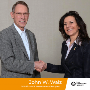 John Walz is congratulated by Computer Society President Cecilia Metra.
