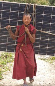 Tibetan child carrying solar panel